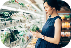 Pregnant woman in the produce aisle of a grocery store