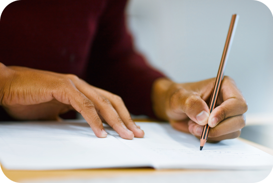 Person sitting at a desk writing with pencil in hand